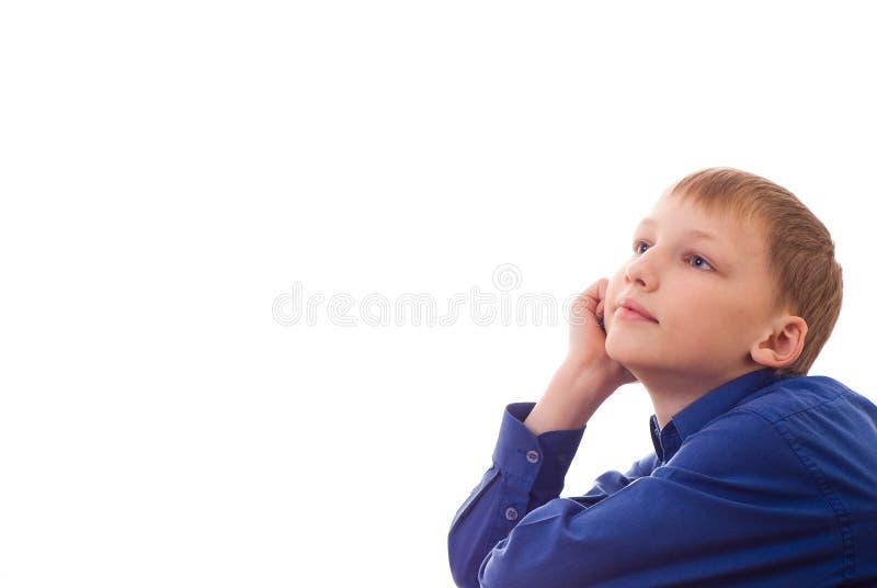 Il ragazzo felice nella camicia blu si siede fotografia stock libera da diritti