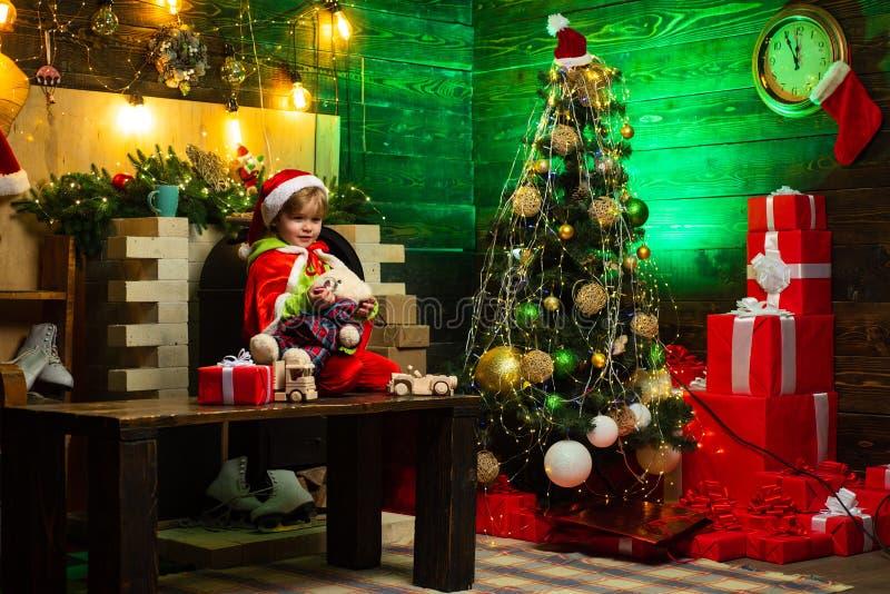 Il ragazzo felice sta giocando con i giocattoli dall'albero di Natale Il bambino sta indossando i vestiti di Santa Il bambino sta fotografie stock libere da diritti