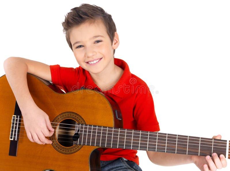 Il ragazzo felice sta giocando sulla chitarra acustica fotografie stock