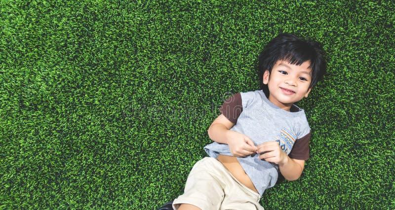 Il ragazzo felice sta trovandosi sul campo di erba del manufatto immagini stock