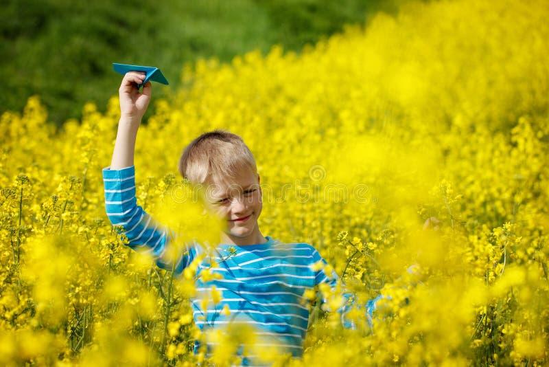 Il ragazzo felice tiene l'aeroplano di carta blu disponibile il giorno soleggiato luminoso fotografie stock