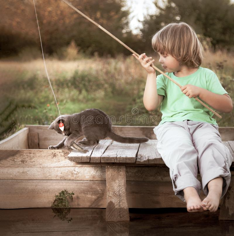 Il ragazzo felice va pescare sul fiume con l'animale domestico, i bambini uno ed il gattino del pescatore con una canna da pesca  fotografia stock libera da diritti