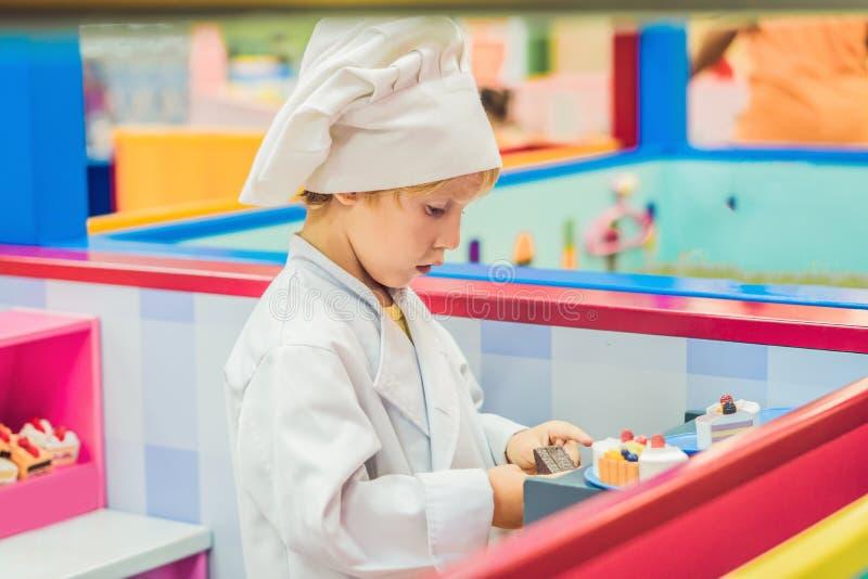 Il ragazzo gioca il gioco come se sia stato un cuoco o un panettiere in una cucina del ` s dei bambini immagine stock libera da diritti