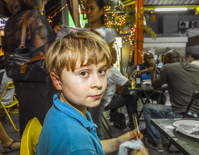 Il ragazzo gode di di mangiare al mercato di notte fotografia stock