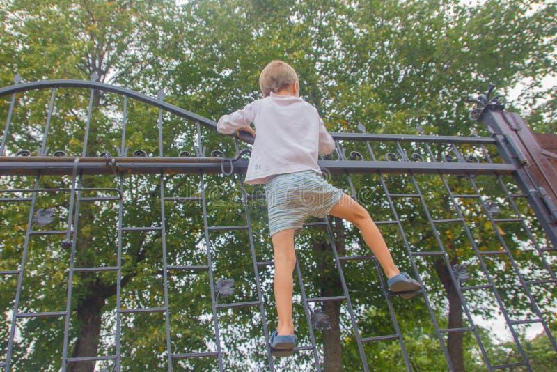 Il ragazzo ha scalato sul recinto Il bambino scala sul portone, Fe immagini stock