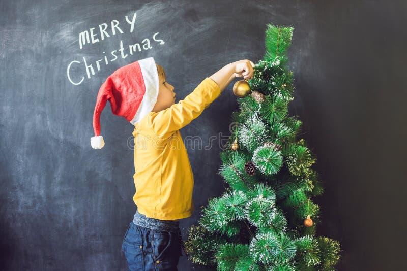 Il ragazzo ha scritto ad un'iscrizione Cristmas allegro Albero di Natale Xma immagini stock