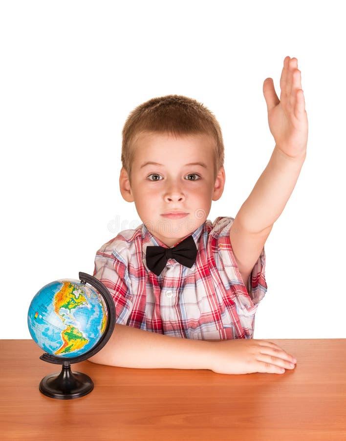 Il ragazzo ha sollevato la sua mano mentre si sedeva alla tavola, vicino al globo, isolato sul bianco immagine stock
