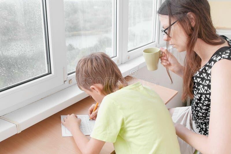 Il ragazzo impara scrivere le lettere che si siedono dalla tavola Fare compito con la sua mamma fotografie stock