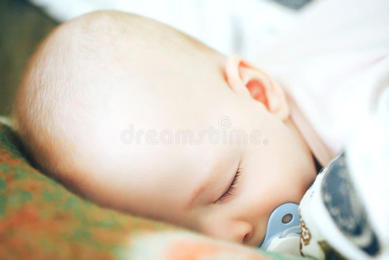 Il ragazzo infantile del bambino del bambino sei mesi sta dormendo a casa fotografia stock