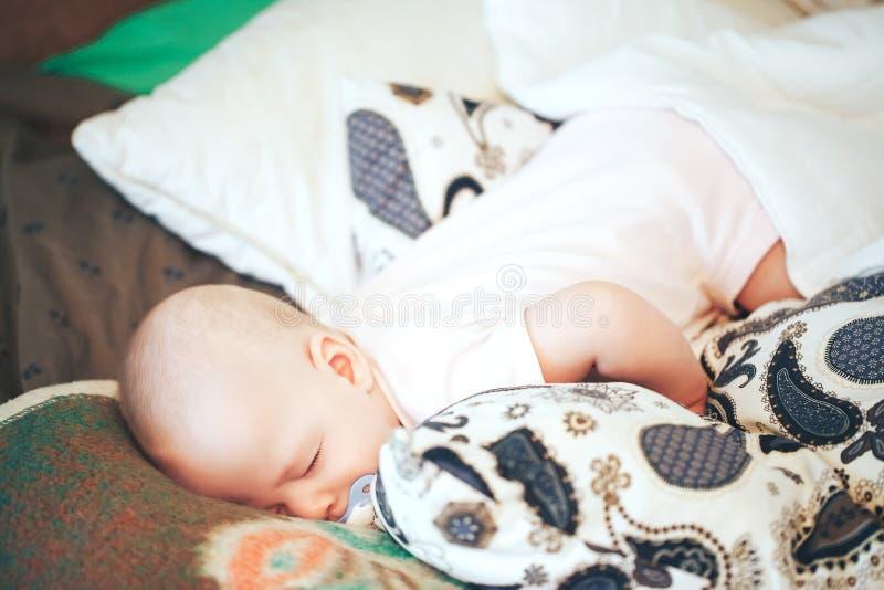 Il ragazzo infantile del bambino del bambino sei mesi sta dormendo a casa immagini stock