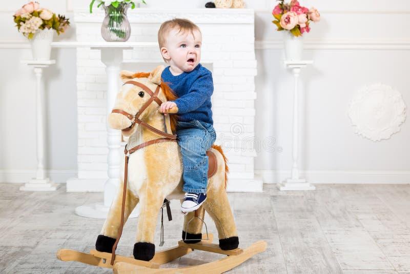 Il ragazzo infantile in maglione e jeans blu si siede su un cavallo del giocattolo Non gradisce che cosa sta accadendo Repulsione fotografia stock libera da diritti
