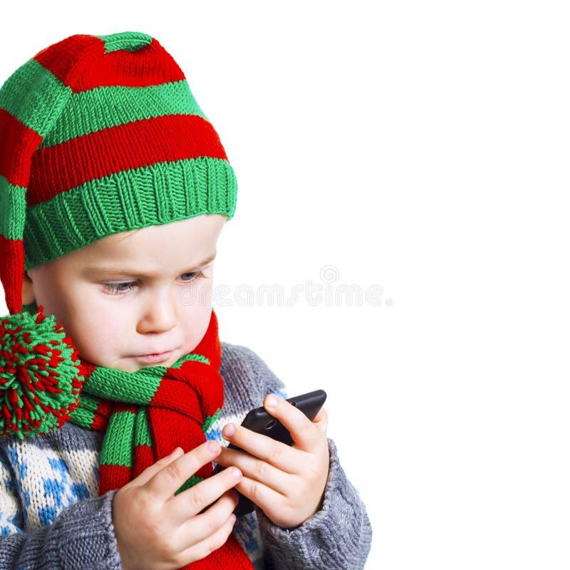Il ragazzo invia un messaggio di testo con un desiderio di Natale a Santa fotografie stock libere da diritti