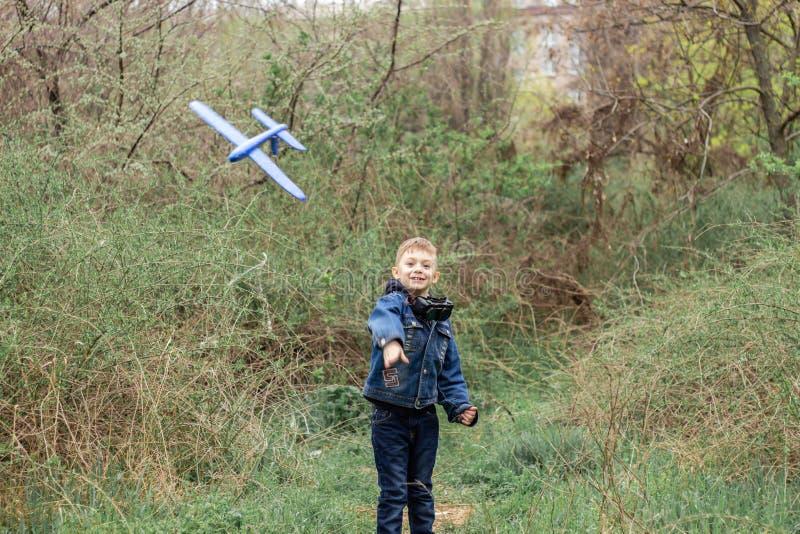 Il ragazzo lancia un aereo blu nel cielo in una foresta densa immagine stock libera da diritti