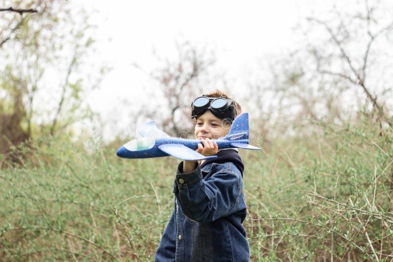 Il ragazzo lancia un aereo blu nel cielo in una foresta densa fotografia stock libera da diritti