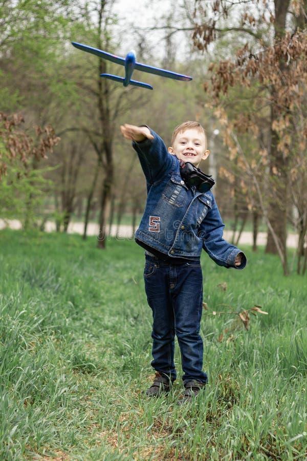 Il ragazzo lancia un aereo blu nel cielo in una foresta densa fotografia stock