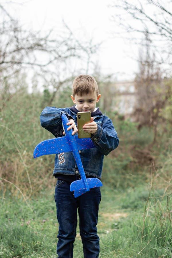 Il ragazzo lancia un aereo blu nel cielo in una foresta densa immagine stock