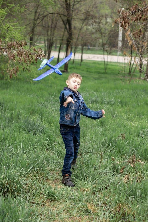 Il ragazzo lancia un aereo blu nel cielo in una foresta densa fotografie stock