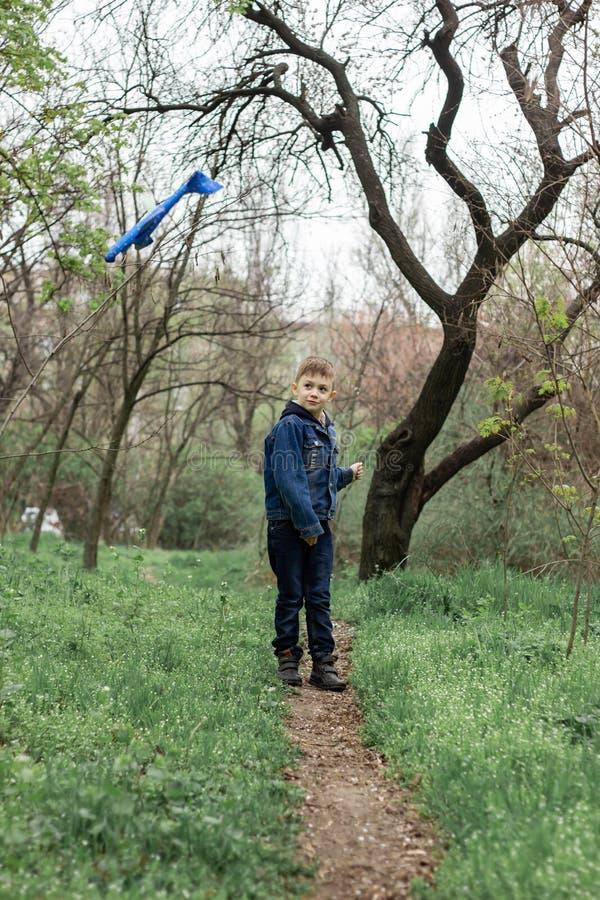 Il ragazzo lancia un aereo blu nel cielo in una foresta densa fotografie stock libere da diritti