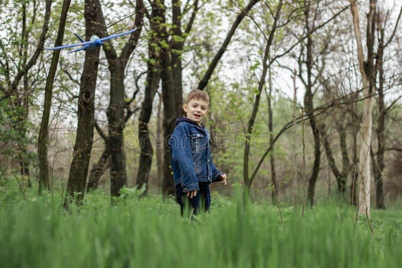 Il ragazzo lancia un aereo blu nel cielo in una foresta densa immagini stock