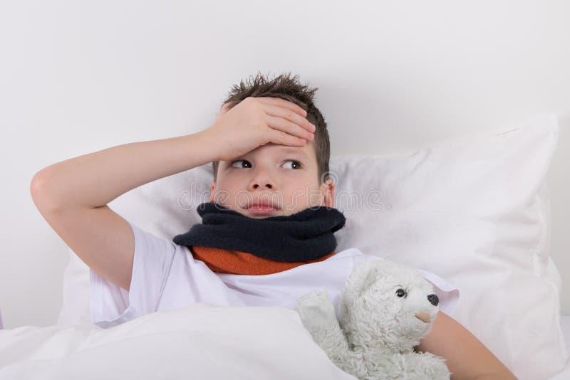 Il ragazzo a letto, il suo ferite della testa fotografia stock