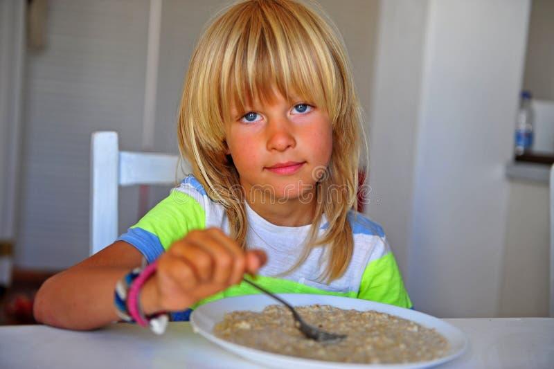 Il ragazzo lungo biondo dei capelli che mangia l'avena si sfalda in cucina fotografie stock libere da diritti