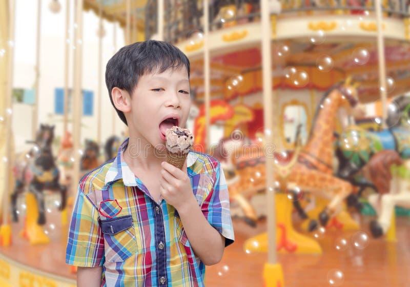 Il ragazzo mangia il gelato davanti ad allegro va giro fotografia stock libera da diritti