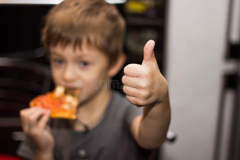 Il ragazzo mangia una pizza molto saporita con grande piacere fotografia stock