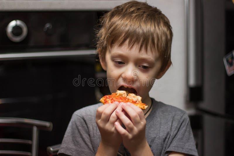 Il ragazzo mangia una pizza molto saporita con grande piacere immagine stock libera da diritti