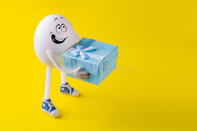 Il ragazzo miniatura divertente dell'uovo di Pasqua dà un presente fotografie stock
