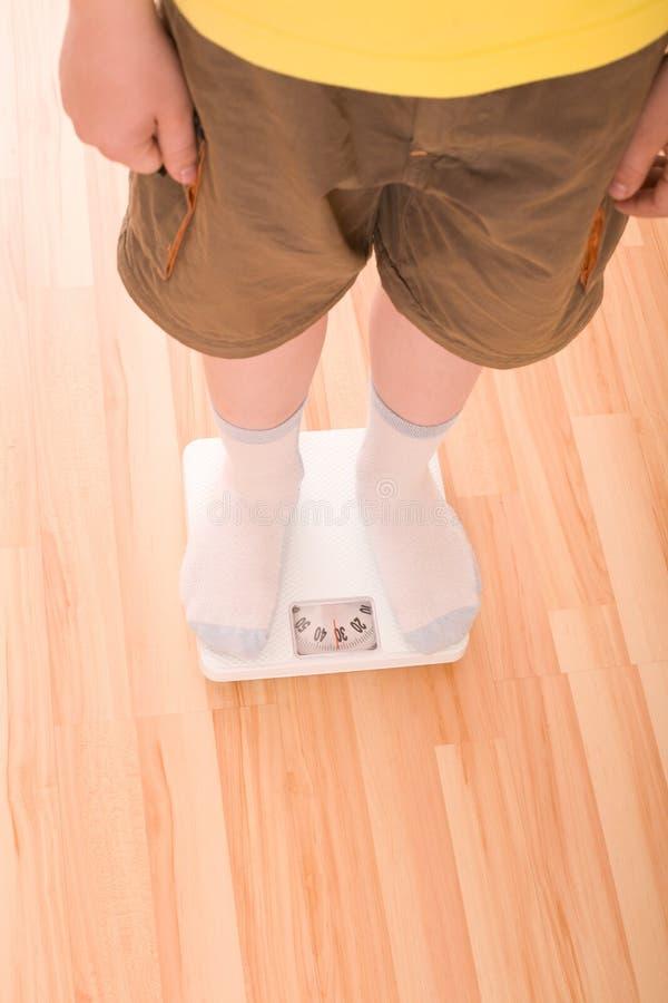 Il ragazzo misura il peso sulle scale del pavimento fotografia stock