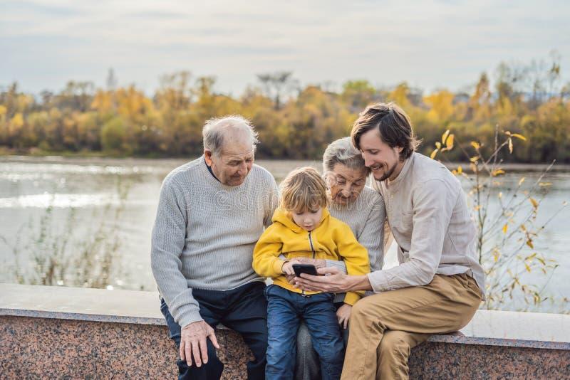 Il ragazzo mostra la foto sul telefono ai suoi nonni fotografia stock libera da diritti