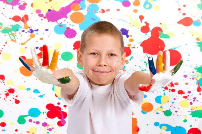 Il ragazzo mostra le sue mani dipinte immagine stock libera da diritti
