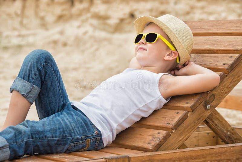 Il ragazzo nel cappello di paglia che si trova sulle chaise-lounge di legno del sole sulla spiaggia Vacanza di estate immagini stock