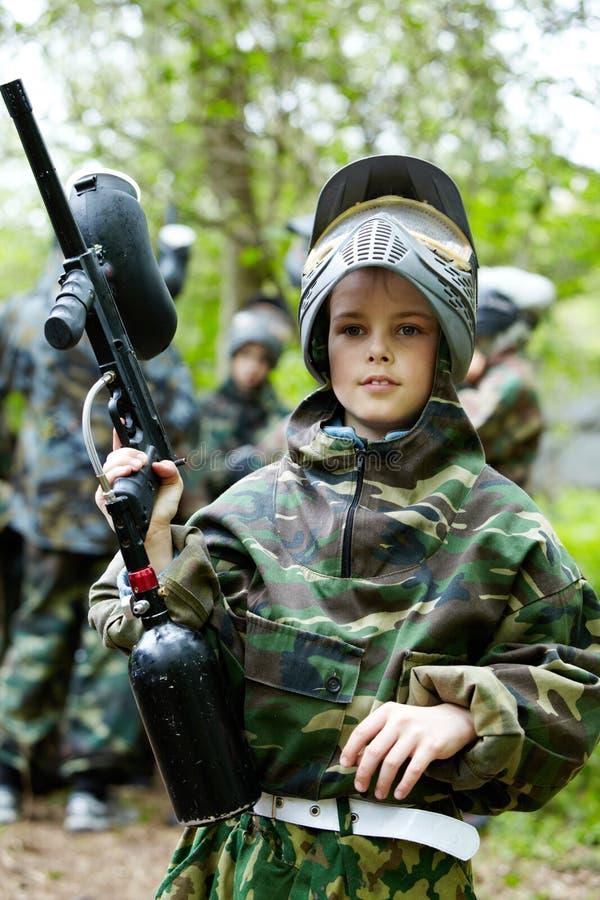 Il ragazzo nel vestito del camuffamento tiene una pistola di paintball fotografie stock libere da diritti