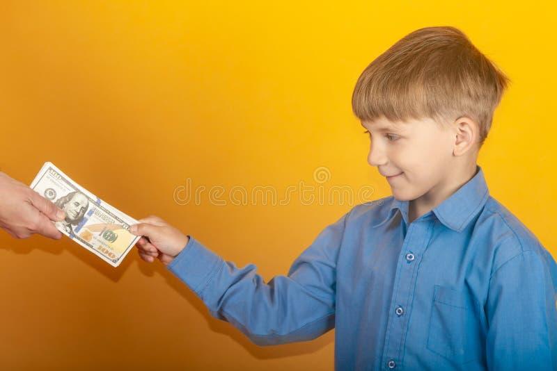 Il ragazzo nella camicia blu allunga fuori la sua mano e prende i dollari immagini stock libere da diritti