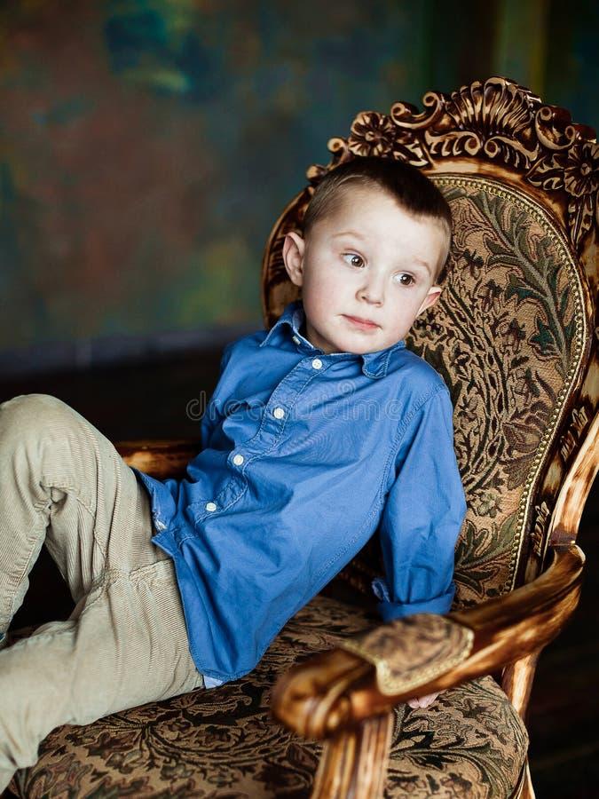 Il ragazzo nella camicia e nel velluto a coste blu ansima immagini stock libere da diritti