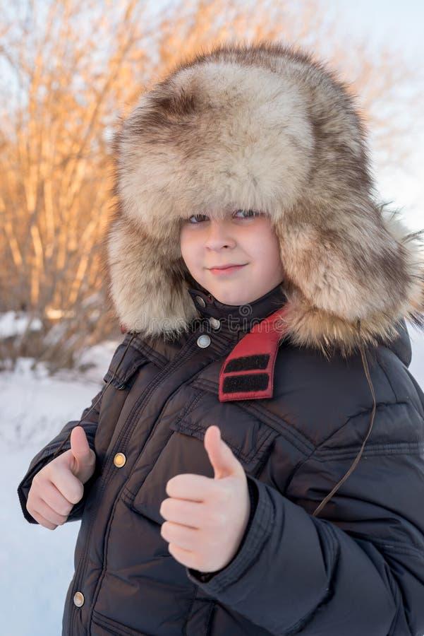 Il ragazzo nelle manifestazioni del cappello dell'inverno gesture tutto è bene fotografia stock libera da diritti