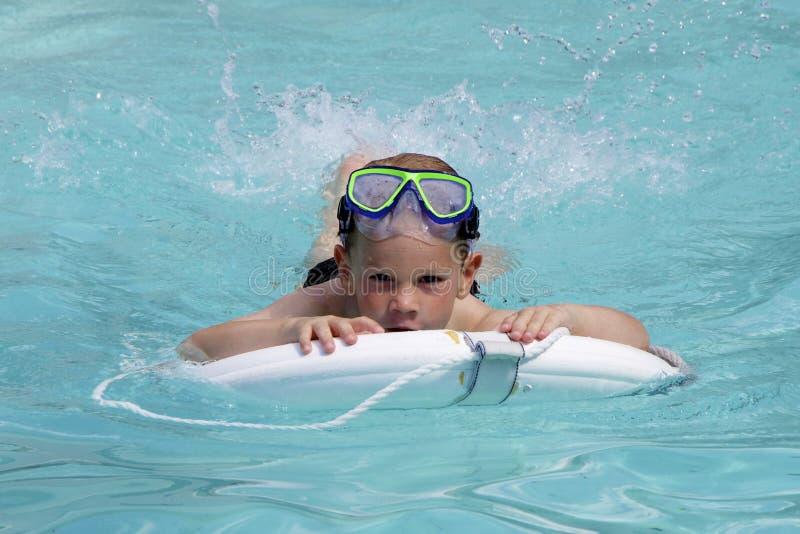 Il ragazzo nuota nell'acqua blu luminosa Front View fotografia stock