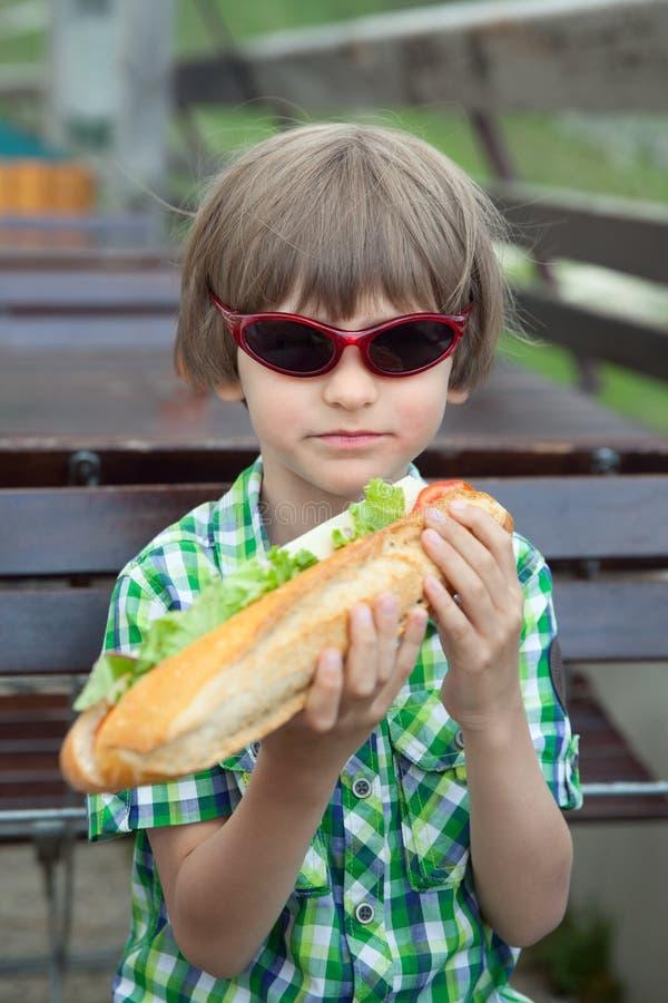 Il ragazzo in occhiali da sole con un grande panino immagini stock