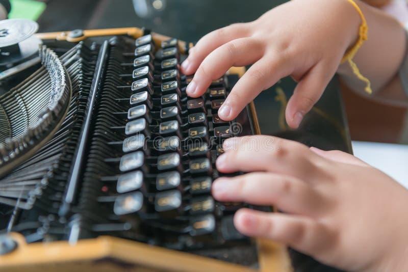 Il ragazzo passa la scrittura sulla vecchia macchina da scrivere immagine stock libera da diritti