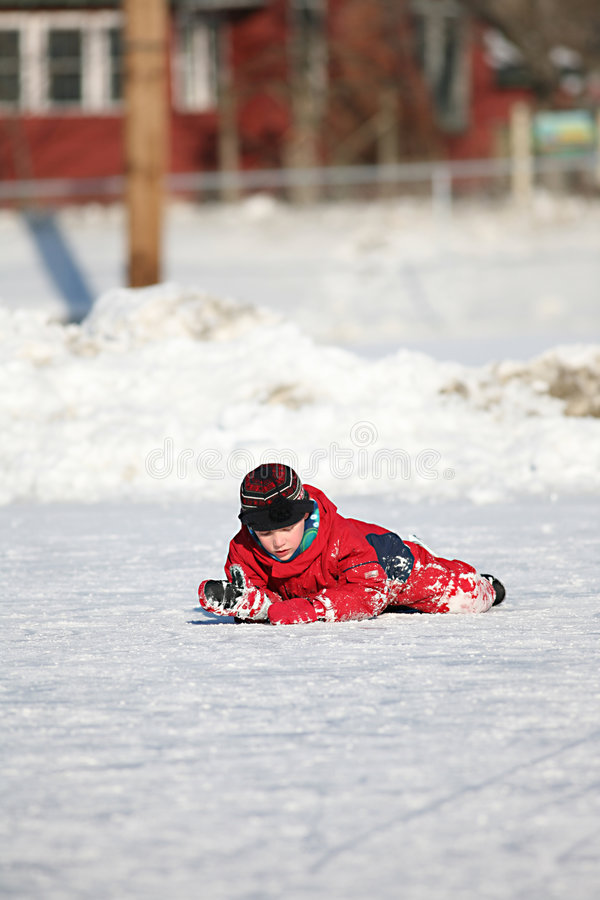 Il ragazzo pattinare di ghiaccio è caduto giù sulla pista di pattinaggio fotografia stock libera da diritti
