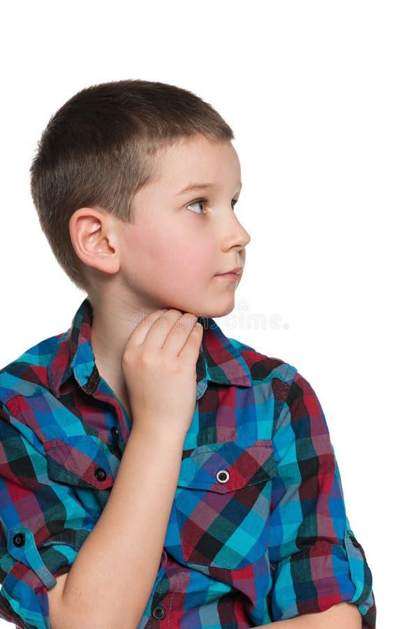 Il ragazzo pensieroso guarda da parte fotografia stock libera da diritti