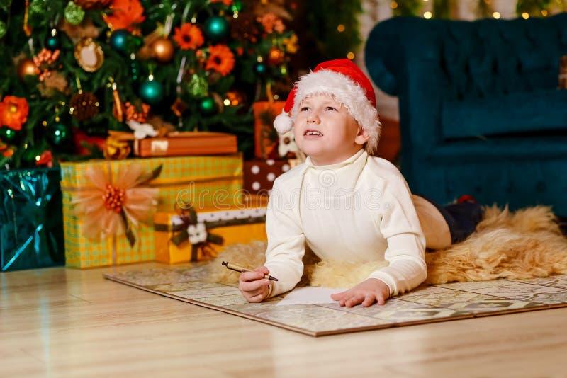 Il ragazzo pensieroso in spiritello malevolo di Santa scrive una lettera a Santa Claus per il Natale sogni fotografia stock