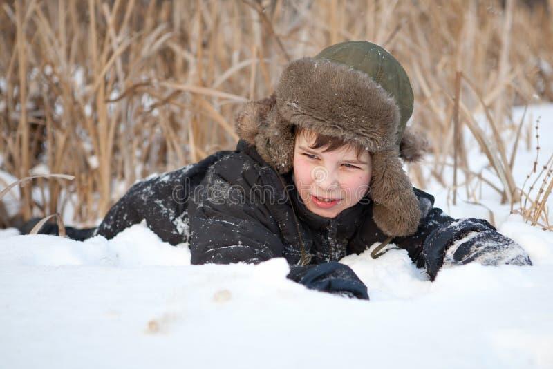 Il ragazzo pone su neve, l'inverno fotografie stock