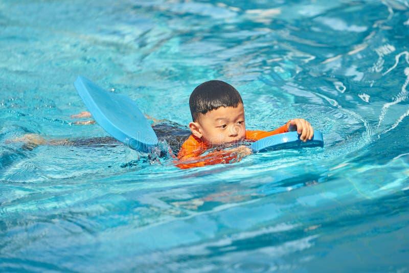 Il ragazzo pratica nuotare con le miodesopsie del cuscinetto di schiuma in acqua fotografie stock