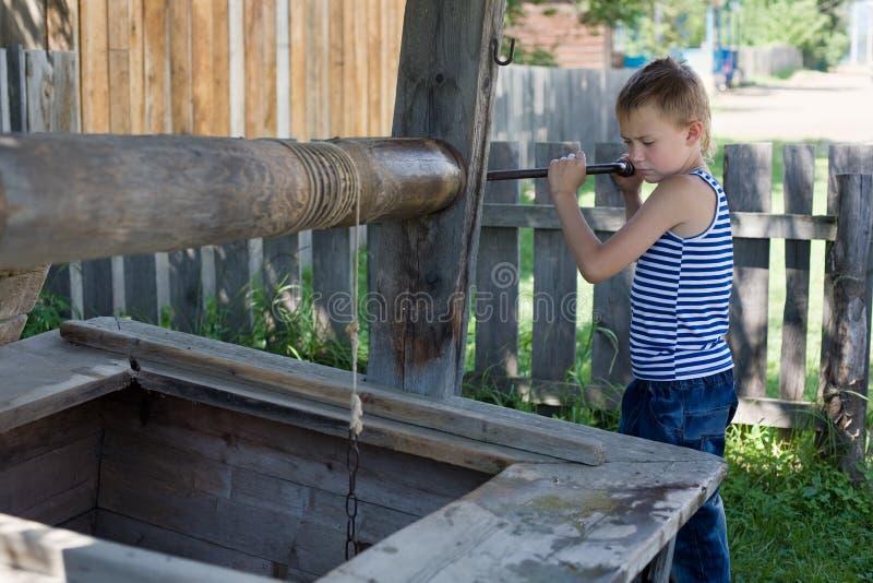 Il ragazzo prende un secchio con acqua fotografie stock
