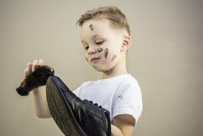 Il ragazzo pulisce le scarpe sporche immagine stock