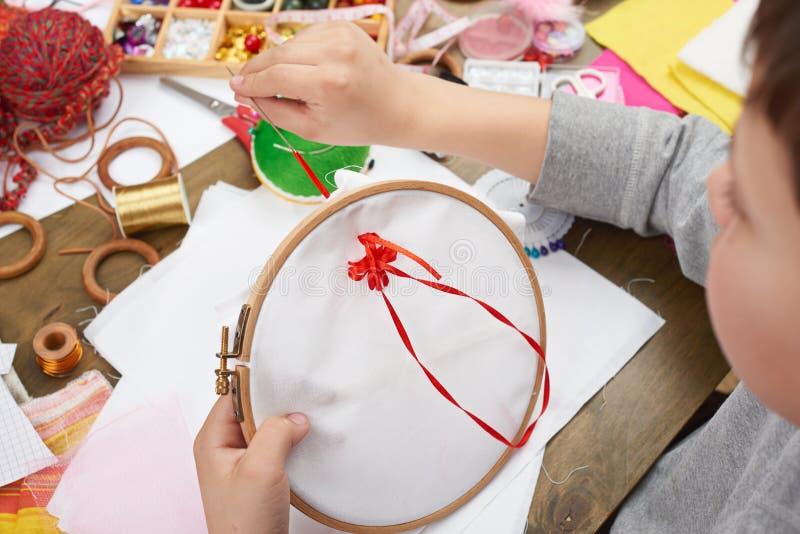 Il ragazzo ricamato sul cerchio, sul primo piano della mano e sul nastro rosso sul tessuto bianco, impara cucire, formazione sul  immagine stock libera da diritti