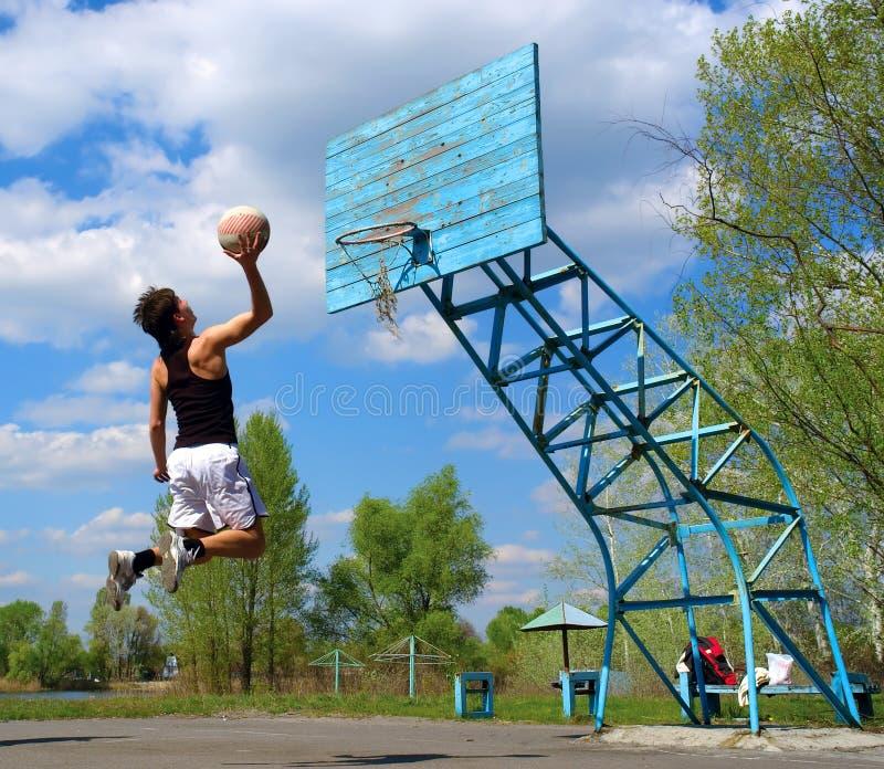 Il ragazzo salta con la sfera di pallacanestro immagini stock
