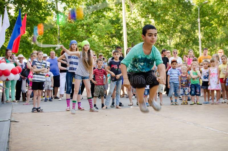 Il ragazzo salta sopra una corda tenuta dalle ragazze in costumi del pirata al partito del pirata fotografie stock